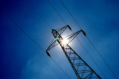 Pylon 09. High voltage electricity pylon over blue sky and sun Royalty Free Stock Image