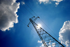 Pylon 11. High voltage electricity pylon over blue sky and white clouds and sun royalty free stock image