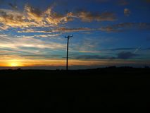 Pylon electric blue sky sunset. Silhouette of a pylon in a field at sunset in the summer Stock Photography