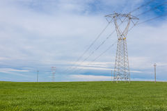 Pylon in the field. An electricity pylon in a green and vibrant field stock images
