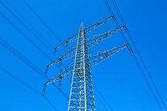 Pylon and high-voltage lines under bright blue sky Stock Photo