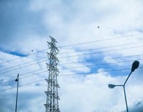 Pylon and  high voltage power line in cloudy sky. Stock Photos