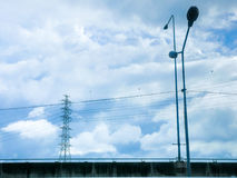 Pylon and  high voltage power line in cloudy sky. Stock Image