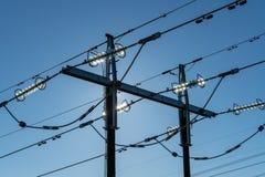 Pylon med höga spänningskraftledningar i ljust solsken arkivbild