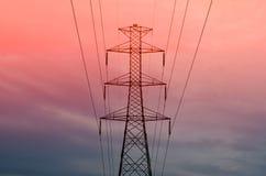 Pylon med kraftledningar mot orange himmel - skymning arkivbilder
