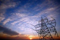 Pylon och kraftledningar på solnedgången Royaltyfri Fotografi