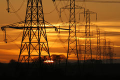 Pylon power. Sun setting behind a row of electricity pylons royalty free stock images