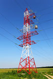 Pylon of power line in the field. With transformer or inductance coil on cables. Red and white metal construction on blue sky background Royalty Free Stock Photo