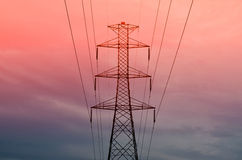 Pylon with power lines against orange sky - twilight Stock Images
