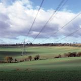 Pylon and power lines. Over field of oil-seed stock photo