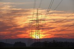 Pylon and power lines at sunrise. With red sky and sun Stock Images