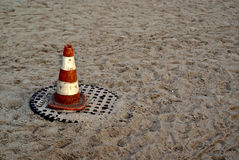 Pylon on Sand. An orange and white pylon sitting on a manhole cover on a sandy beach stock photography
