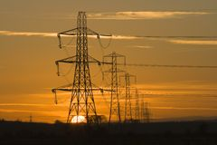 Pylon sunset. Sun setting behind a row of electricity pylons stock image