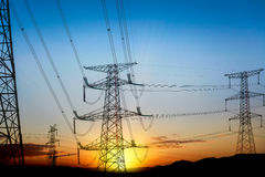 Pylon at sunset. High voltage electricity transmission pylon silhouetted at sunset stock photos