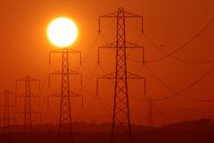Pylon sunshine. Sun above a row of electricity pylons stock image