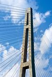 Pylonen kabel-blev bron mot bakgrunden av en molnig himmel Arkivfoto