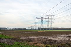 Pylonen met hoog voltage en lijnen met hoog voltage voor het vervoeren van elektriciteit van de elektrische centrale op de achter royalty-vrije stock afbeelding