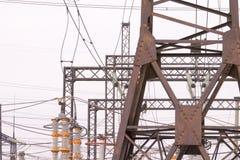 Pyloner och elkraften binder på station för elkraftfördelning Arkivfoton