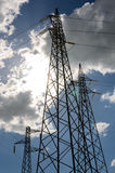 Pylons. In backlight against a cloudy and blue sky Royalty Free Stock Photography