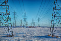 Pylons on a blue sky. Group of high-voltage electricity power pylons over blue sky and snow covered countryside, Canada Stock Image