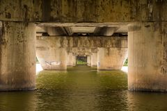 Pylons or concrete pillar of the bridge in the water of the river, facing each other in a staggered downward recessive manner as a. Portal to another location Royalty Free Stock Image