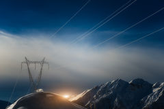 Pylons covered with snow. In the high mountains carry energy downstream Stock Photo