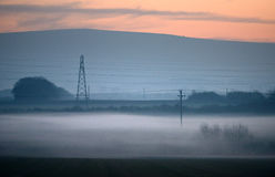 Pylons. Electricity pylons at dusk with low lying mist Royalty Free Stock Photography