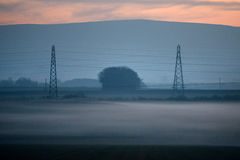 Pylons. Electricity pylons at dusk with low lying mist Royalty Free Stock Photo