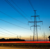 Pylons and electricity power lines at night with traffic lights. Royalty Free Stock Image