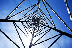 Pylons. Electricity pylon from below and lines against blue sky Stock Photography