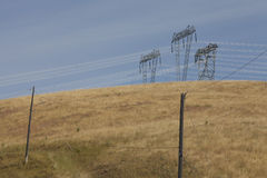 Pylons in a field. Pylons in a golden field. Pylons on the hill Royalty Free Stock Photo