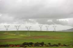 Pylons. In green field on an overcast day Royalty Free Stock Photography