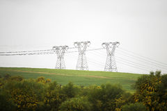 Pylons. In green field on an overcast day Stock Photos