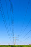 Pylons and high-voltage lines under bright blue sky Stock Photo