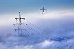 Pylons in the mist. Pylons and cables emerging from the cloud Stock Photo