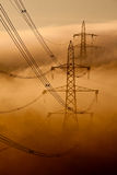 Pylons in the mist. Pylons and cables emerging from the cloud Royalty Free Stock Images