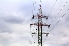 Pylons and power lines with vibrant sky, clouds and sun. Royalty Free Stock Image