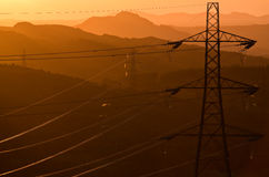Pylons for power. Steel power carrying pylons against the setting sun Royalty Free Stock Photos