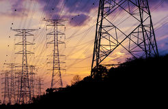 Pylons. Silhouette electricity pylons in sunset background Royalty Free Stock Photo