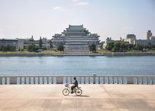 09/09/2018: Pyongyang, Coreia do Norte: um ciclista só que passa Kim Il Sung Palace imagem de stock