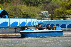 Pyongyang, North Korea. Taesongsan Park. Pyongyang, North Korea - May 1, 2019: Happy family in boat riding on water attraction in the Taesongsan Funfair. Is an royalty free stock image