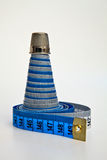 A pyramid. A pyramid made from two measurement tapes swirled together with thimble on its top Royalty Free Stock Photography