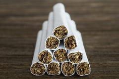 Pyramid av cigaretter på den gamla wood tabellen Arkivfoton