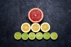 Pyramid av den klippta citroner, limefrukter och grapefrukten på svart bakgrund Royaltyfria Foton