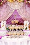 Pyramid av exponeringsglas med champagne i purpurfärgad bröllopinre Arkivfoton