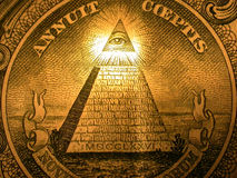 Pyramid on back of dollar. A closeup of the pyramid design on the back of an American dollar bill. It shows an eye being illuminated by light at the top of the Stock Photography