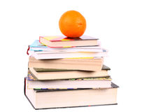 Pyramid of books with orange on the top Stock Images