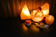 Pyramid, Bowl Chunks & Natural Salt Lamps | Himalayan Salt. Glowing Pyramid, Bowl Chunks & Natural Salt Lamps with wooden & black background. Natural salt lamps stock photos