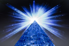 Pyramid and the bright flash of a star in space. Blue pyramid with neon lights and bright flash of stars in space on a dark gray background stock images