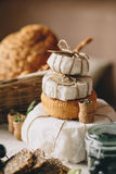 Pyramid cake from cheese heads, near bread, glass jar, cork from wine Royalty Free Stock Image